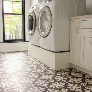 Large elegant single-wall ceramic tile and brown floor dedicated laundry room photo in Other with an undermount sink, recessed-panel cabinets, white cabinets, quartz countertops, white walls and a side-by-side washer/dryer