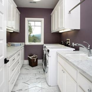Bild på en vintage tvättstuga, med lila väggar, vita skåp och vitt golv
