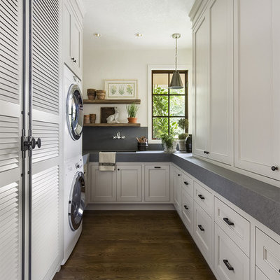 Example of a classic u-shaped dark wood floor laundry room design in Portland with an undermount sink, recessed-panel cabinets, white cabinets, white walls, a stacked washer/dryer and gray countertops