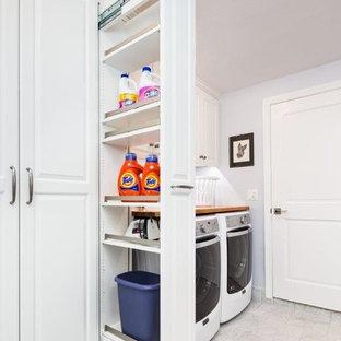 Foto di una lavanderia multiuso classica di medie dimensioni con ante bianche, top in legno, lavatrice e asciugatrice affiancate, ante con bugna sagomata e pareti grigie