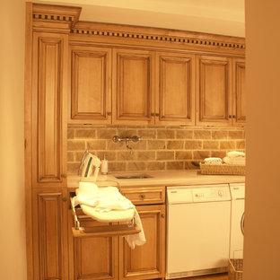 Inredning av ett klassiskt litet linjärt grovkök, med en enkel diskho, luckor med upphöjd panel, marmorbänkskiva, ljust trägolv, en tvättmaskin och torktumlare bredvid varandra, skåp i mellenmörkt trä och bruna väggar