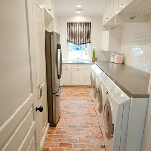 This is an example of a traditional laundry room in Houston with brick floors and red floor.