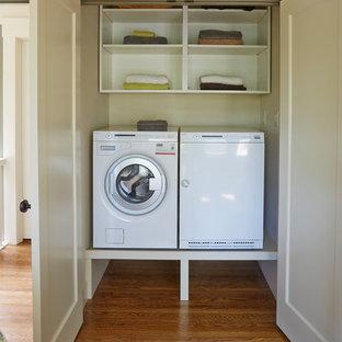Foto på en mellanstor vintage linjär liten tvättstuga, med öppna hyllor, vita skåp, vita väggar, mellanmörkt trägolv och en tvättmaskin och torktumlare bredvid varandra