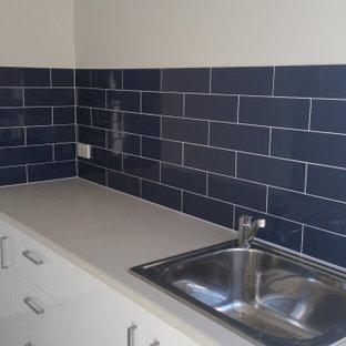 Immagine di una lavanderia con ante bianche, top in laminato, paraspruzzi blu, paraspruzzi con piastrelle diamantate, pavimento con piastrelle in ceramica, pavimento grigio e top beige