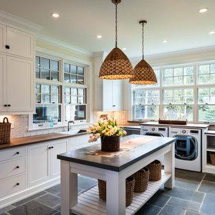 ミルウォーキーの巨大なトラディショナルスタイルのおしゃれな洗濯室 (シングルシンク、シェーカースタイル扉のキャビネット、白いキャビネット、ベージュの壁、左右配置の洗濯機・乾燥機、グレーの床、木材カウンター、スレートの床、茶色いキッチンカウンター) の写真