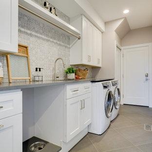 Foto di una grande sala lavanderia tradizionale con lavello sottopiano, ante in stile shaker, ante bianche, top in quarzo composito, pareti beige, pavimento in gres porcellanato, lavatrice e asciugatrice affiancate, pavimento grigio e top grigio