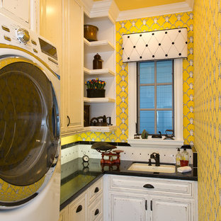 Mid-sized elegant l-shaped limestone floor and black floor dedicated laundry room photo in Orange County with an undermount sink, raised-panel cabinets, distressed cabinets, yellow walls, a stacked washer/dryer, quartz countertops and black countertops