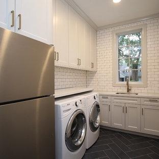 Esempio di una sala lavanderia chic di medie dimensioni con lavello sottopiano, ante in stile shaker, ante bianche, top in quarzo composito, pareti grigie, pavimento in cemento, lavatrice e asciugatrice affiancate e pavimento nero