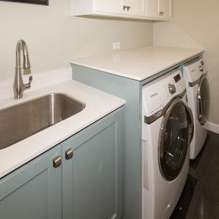 Klassisk inredning av en mellanstor parallell tvättstuga enbart för tvätt, med en undermonterad diskho, skåp i shakerstil, bänkskiva i kvarts, grå väggar, mörkt trägolv, en tvättmaskin och torktumlare bredvid varandra och blå skåp