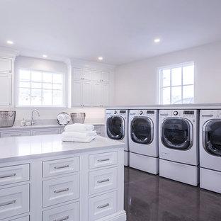 Idéer för en mycket stor klassisk u-formad tvättstuga enbart för tvätt, med skåp i shakerstil, vita skåp, bänkskiva i koppar, vita väggar, mörkt trägolv, en tvättmaskin och torktumlare bredvid varandra och brunt golv