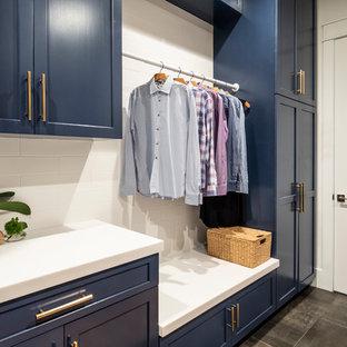 Foto di una sala lavanderia chic di medie dimensioni con lavello sottopiano, ante in stile shaker, ante blu, top in superficie solida, pareti bianche, pavimento in cemento, lavatrice e asciugatrice affiancate, pavimento grigio e top bianco