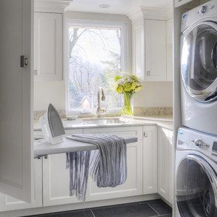 Esempio di una sala lavanderia classica di medie dimensioni con lavatrice e asciugatrice a colonna, ante bianche, lavello sottopiano, ante con riquadro incassato, top in granito, pavimento in ardesia e top beige