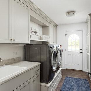 Klassisk inredning av ett stort grå parallellt grått grovkök, med en nedsänkt diskho, släta luckor, vita skåp, bänkskiva i kvarts, grå väggar, mörkt trägolv, en tvättmaskin och torktumlare bredvid varandra och brunt golv