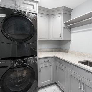 Foto di una sala lavanderia classica di medie dimensioni con lavello sottopiano, ante con riquadro incassato, ante grigie, top in quarzo composito, pareti grigie, moquette, lavatrice e asciugatrice a colonna, pavimento beige e top bianco