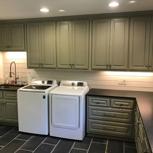 Inspiration for a large classic l-shaped separated utility room in Other with a submerged sink, raised-panel cabinets, green cabinets, white walls, a side by side washer and dryer, black floors, black worktops and soapstone worktops.