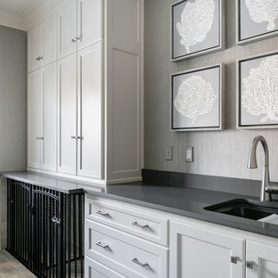 Photo of a large traditional galley utility room in Kansas City with a submerged sink, beaded cabinets, white cabinets, engineered stone countertops, grey walls, porcelain flooring, a side by side washer and dryer, grey floors and grey worktops.