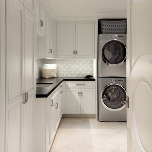 Design ideas for a traditional l-shaped separated utility room in Miami with a submerged sink, recessed-panel cabinets, white cabinets, a stacked washer and dryer, beige floors and black worktops.