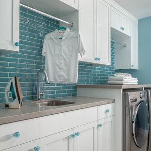 Inspiration för en vintage grå linjär grått tvättstuga enbart för tvätt, med en undermonterad diskho, skåp i shakerstil, vita skåp, blå väggar, en tvättmaskin och torktumlare bredvid varandra och grått golv