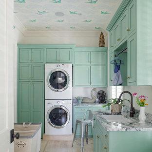 Cette image montre une buanderie traditionnelle dédiée avec un évier 2 bacs, un placard à porte shaker, un sol en bois clair, des machines superposées et des portes de placard bleues.