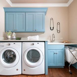 Exempel på en liten klassisk vita linjär vitt tvättstuga enbart för tvätt, med skåp i shakerstil, blå skåp, bänkskiva i kvarts, beige väggar, mellanmörkt trägolv, en tvättmaskin och torktumlare bredvid varandra, en nedsänkt diskho och brunt golv