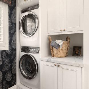 Idéer för att renovera en vintage vita vitt tvättstuga, med luckor med infälld panel, vita skåp, svarta väggar, en tvättpelare och brunt golv
