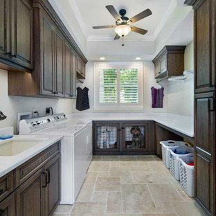 Bild på ett stort vintage vit u-format vitt grovkök, med en undermonterad diskho, luckor med upphöjd panel, skåp i mörkt trä, bänkskiva i kvarts, beige stänkskydd, beige väggar, travertin golv, en tvättmaskin och torktumlare bredvid varandra och beiget golv