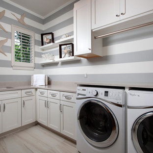 Inspiration for a mid-sized transitional l-shaped dedicated laundry room remodel in Miami with an undermount sink, shaker cabinets, white cabinets, gray walls and a side-by-side washer/dryer