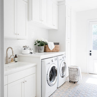 Cette image montre une buanderie traditionnelle avec un évier encastré, un placard à porte shaker, des portes de placard blanches, un mur blanc, des machines côte à côte, un sol multicolore et un plan de travail blanc.