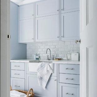 Foto di una sala lavanderia chic con lavello stile country, ante con riquadro incassato, top in marmo, pavimento con piastrelle in ceramica, ante blu, pavimento bianco e top bianco