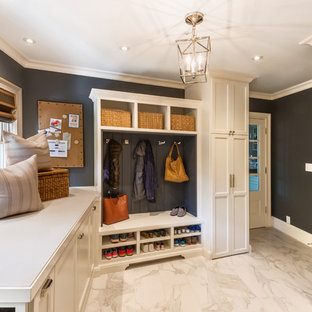 Design ideas for a large transitional l-shaped utility room in San Francisco with shaker cabinets, white cabinets, a farmhouse sink, solid surface benchtops, grey walls, marble floors and a stacked washer and dryer.