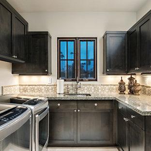 Idéer för en mellanstor klassisk u-formad tvättstuga enbart för tvätt, med en undermonterad diskho, skåp i shakerstil, granitbänkskiva, ljust trägolv, en tvättmaskin och torktumlare bredvid varandra, vita väggar, beiget golv och skåp i mörkt trä
