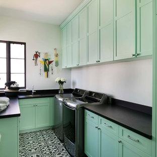 Immagine di una sala lavanderia mediterranea con lavello sottopiano, ante in stile shaker, ante verdi, pareti bianche, lavatrice e asciugatrice affiancate e pavimento multicolore