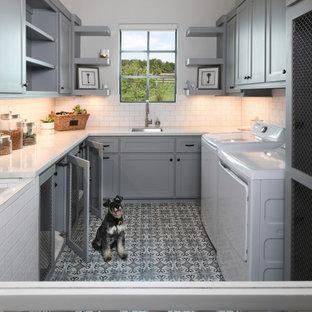 Bild på en mellanstor vintage vita u-formad vitt tvättstuga enbart för tvätt, med en allbänk, skåp i shakerstil, grå skåp, vitt stänkskydd, stänkskydd i tunnelbanekakel, vita väggar, klinkergolv i porslin, en tvättmaskin och torktumlare bredvid varandra och flerfärgat golv