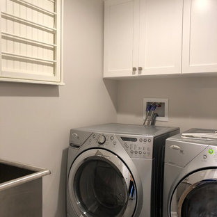 Example of a large transitional l-shaped dark wood floor and brown floor dedicated laundry room design in New York with a farmhouse sink, shaker cabinets, white cabinets, quartz countertops, white backsplash, ceramic backsplash, white countertops, gray walls and a side-by-side washer/dryer