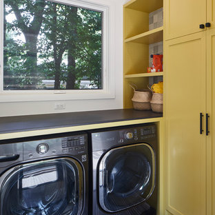 Mid-sized transitional l-shaped dedicated laundry room photo in Austin with shaker cabinets, yellow cabinets, white walls, a side-by-side washer/dryer and gray countertops