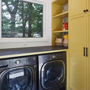 Inspiration för en mellanstor vintage grå l-formad grått tvättstuga enbart för tvätt, med skåp i shakerstil, gula skåp, vita väggar och en tvättmaskin och torktumlare bredvid varandra