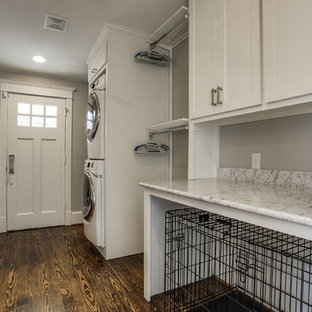 This is an example of a large traditional galley utility room in Dallas with shaker cabinets, white cabinets, marble worktops, grey walls, dark hardwood flooring, a stacked washer and dryer and white worktops.
