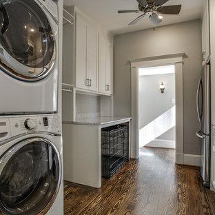 Ejemplo de lavadero multiusos y de galera, clásico renovado, grande, con fregadero sobremueble, armarios estilo shaker, puertas de armario blancas, encimera de mármol, paredes grises, suelo de madera oscura y lavadora y secadora apiladas