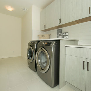 Large contemporary single-wall dedicated laundry room in Edmonton with an undermount sink, flat-panel cabinets, light wood cabinets, laminate benchtops, white walls, ceramic floors and a side-by-side washer and dryer.