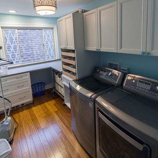 Esempio di una sala lavanderia contemporanea di medie dimensioni con lavello sottopiano, ante con riquadro incassato, ante bianche, top in quarzo composito, pareti blu, pavimento in bambù e lavatrice e asciugatrice affiancate