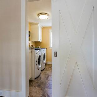 Exempel på en mellanstor klassisk parallell tvättstuga enbart för tvätt, med luckor med infälld panel, vita skåp, bänkskiva i kvartsit, skiffergolv, en tvättmaskin och torktumlare bredvid varandra och orange väggar
