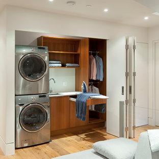 Idées déco pour une buanderie linéaire contemporaine avec un placard, un évier encastré, un placard à porte plane, des portes de placard en bois brun, un mur blanc, un sol en bois brun, des machines superposées et un plan de travail blanc.