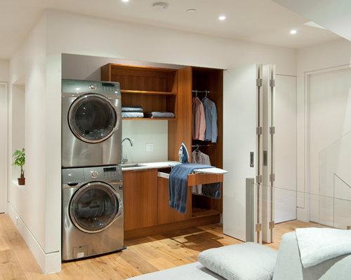Hauswirtschaftsraum mit waschmaschinenschrank und weißer wandfarbe