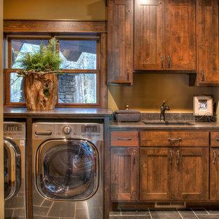 Bild på en mellanstor rustik grå linjär grått tvättstuga enbart för tvätt, med en undermonterad diskho, skåp i mellenmörkt trä, granitbänkskiva, skiffergolv, en tvättmaskin och torktumlare bredvid varandra, grått golv, skåp i shakerstil och bruna väggar