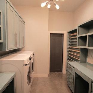 Immagine di una grande lavanderia multiuso stile americano con ante in stile shaker, ante blu, top in legno, pareti beige, pavimento in cemento, lavatrice e asciugatrice affiancate, pavimento grigio e top blu