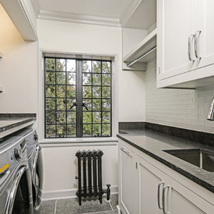 This is an example of a small traditional single-wall separated utility room in New York with a submerged sink, shaker cabinets, grey cabinets, limestone worktops, grey walls, limestone flooring, a side by side washer and dryer, black floors and black worktops.
