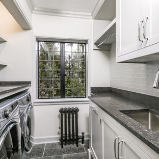 Small classic single-wall separated utility room in New York with a submerged sink, shaker cabinets, grey cabinets, limestone worktops, grey walls, limestone flooring, a side by side washer and dryer, black floors and black worktops.