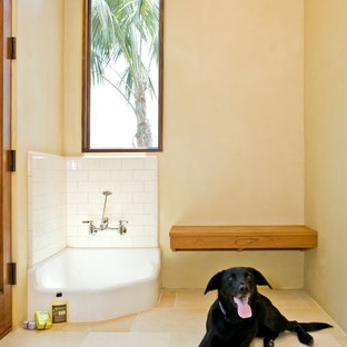 This is an example of a large tropical l-shaped utility room in Santa Barbara with yellow walls, beige floor, an undermount sink, shaker cabinets, white cabinets, travertine floors, a side-by-side washer and dryer and white benchtop.