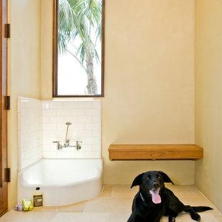 Foto di una grande lavanderia multiuso tropicale con pareti gialle, pavimento beige, lavello sottopiano, ante in stile shaker, ante bianche, pavimento in travertino, lavatrice e asciugatrice affiancate e top bianco