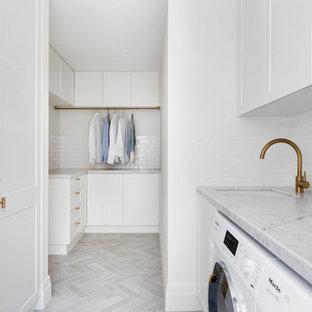 Idéer för en mellanstor maritim grå l-formad tvättstuga enbart för tvätt, med en nedsänkt diskho, skåp i shakerstil, vita skåp, marmorbänkskiva, vitt stänkskydd, stänkskydd i tunnelbanekakel, vita väggar, klinkergolv i keramik, en tvättmaskin och torktumlare bredvid varandra och grått golv